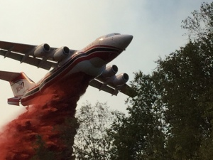An air tanker drops retardant near a cabin at Healy Lake on Wednesday as part of an effort to protect cabins around the remote lake approximately 30 miles south of Delta Junction. Photo by Bob Hajdukovich.