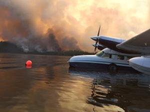 The Healy Lake Fire burns along the edge of Healy Lake on Wednesday as a plane sits parked on the lake. Photo by Bob Hajdukovich.