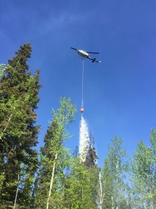 A helicopter drops a 300-gallon bucket of water on the Ohio Creek Fire off Standard Creek Road, about 20 miles southwest of Fairbanks on Thursday afternoon. Tasha Shields/Alaska Division of Forestry