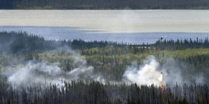 A helicopter equipped with a water dropping bucket douses hotspots on the Tetlin River Fire on Tuesday, June 21, 2016. Photo by Sam Harrel/Alaska Division of Forestry
