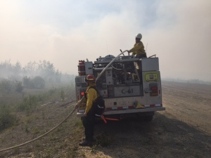 Jenny Moser, front, and Ashley Dale, on truck, man engine C-61 during the Tetlin River Fire near Tok two weeks ago.