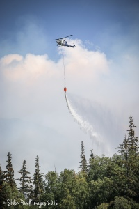 A helicopter with a Bambi bucket drops water on the McHugh Fire burning near the McHugh Creek Trail in Chugach State Park on Sunday, July 17, 2016. Photo by Shiloh Powell