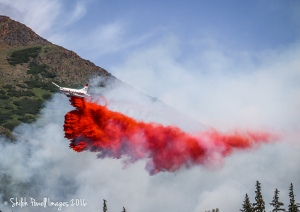 A Convair CV580 air tanker from the Alaska Division of Forestry drops a load of retardant on the 60-acre McHugh Fire on Sunday, July 17, 2016. A total of 18 loads of retardant were dropped on the fire Sunday and tankers returned Monday to drop more tetardant on the fire burning near the McHugh Creek Trail in Chugach State Park. Photo by Shiloh Powell
