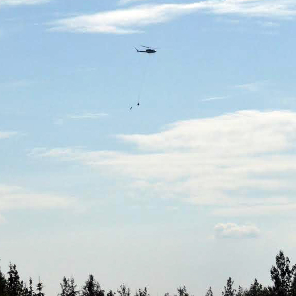 A BLM Alaska Fire Service helicopter carries supplies to firefighters working on fires within the Alatna Complex. Most supplies are delivered via sling loads that are carried in by helicopters. Before the supplies are broken into sling loads they are first delivered to the Allakaket airport, then separated based on where they are to be delivered.