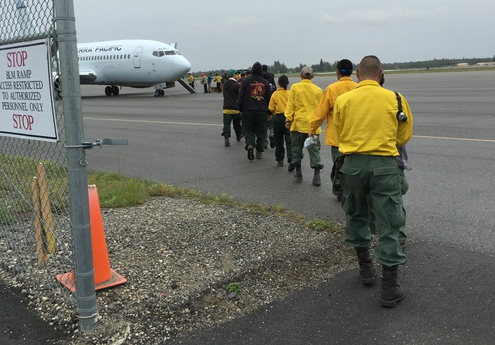 Emergency firefighter crews from Chevak, Hooper Bay, Huslia and Kaltag line up to board a jet that will take them to the Lower 48 to work on wildland fires. Photo by Darla Theisen/Alaska Division of Forestry