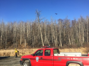 A helicopter with a water bucket flies over the Moose Creek Fire about 5 miles south of Sutton on Saturday afternoon near the area being used as a staging area for firefighters. Photo by Sarah Saarloos/Alaska Division of Forestry