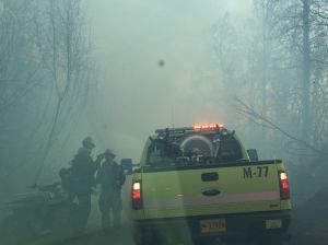 Two firefighters talk to a crew in a Division of Forestry engine on Sunday at the Moose Creek Fire near Sutton. The fire is now estimated at 300 acres and is 25 percent contained. Photo by Sarah Saarloos/Alaska Division of Forestry