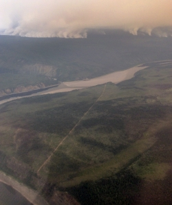 The Campbell River Fire burns to the southwest of the confluence of the Salmon Trout and Porcupine rivers Thursday, July 13, 2017, near the Canadian border in northeast Alaska. A fire break is visible in the foreground cut to protect Native allotments and the historic area of Old Rampart, an area from the days of riverboat trade between fur buyers and local trappers. James Higgins / BLM Alaska Fire Service