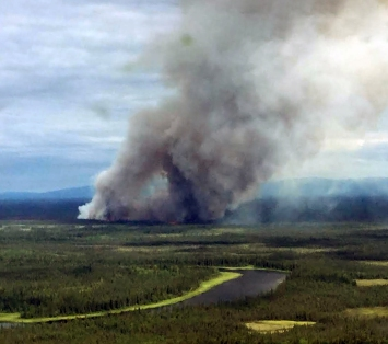 The Khotol Fire burning 14 miles east of Kaltag roared back to life on Tuesday, putting up smoke and prompting fire officials to send 16 smokejumpers to provide protection for a cabin and two Native allotments burning nearby. Photo Courtesy Doug Downes//BLM Alaska Fire Service