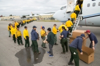 Members of the BLM Alaska Fire Service's training crew, the North Star Fire Crew, hand two sack lunches to each firefighter boarding a jet bound for Missoula, Montana on Aug. 11, 2017. Photo by Beth Ipsen//BLM Alaska Fire Service
