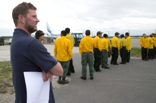 BLM Alaska Fire Service Safety Manager Doug Mackey watches as crew members line up to load bags on a jet bound for Missoula, Montana on Aug. 11, 2017. Mackey was assigned as an interagency resource representative to the four crews that left on the plane that morning. Photo by Beth Ipsen//BLM Alaska Fire Service