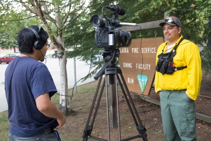 KTVF Fairbanks reporter David Spindler interviews Selawik Crew Boss in training, Joseph Aray, before Aray and 80 other firefighters board a jet bound for Missoula, Montana on Aug. 11, 2017 to help with the busy fire season in the Lower 48. Photo by Beth Ipsen//BLM Alaska Fire Service