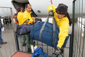 Upper Kalskag crew members William Alexie, on right, and Francis Vaska load bags on a jet bound for Missoula, Montana on Aug. 11, 2017. Photo by Beth Ipsen//BLM Alaska Fire Service