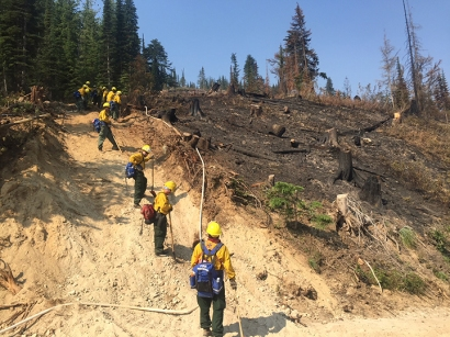 Photo of the K-River crew with firefighters from Allakaket and Hughes grinding the black on a fire in the Lower 48 this summer.