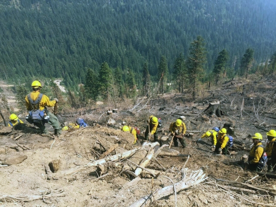 Photo of Members of the K-River Crew made up of firefighters from Hughes and Allakaket mop up a fire in the Lower 48 during the 2018 fire season.