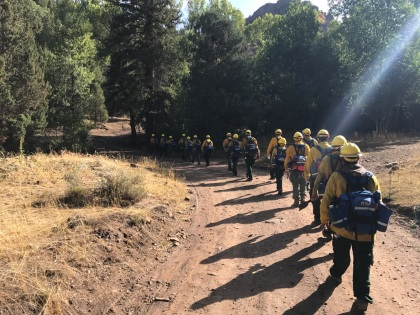 Photo of Emergency firefighters on the Yukon Flats crew walk to the fireline while on a fire in the Lower 48 in 2018.