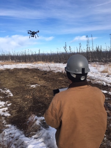 Photo of drone pilot Dustin Wessel operating a quadcopter to help monitor the prescribed burn.