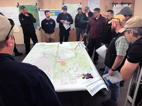Photo of Casey Boespflug, with pointer, briefs a group of representatives from the BLM Eastern Interior Field Office, State of Alaska, Department of Defense, the Alaska Wildland Fire Coordinating Group, on a strategic plan the Alaska Incident Management Team has been working on for the past few days. Photo by Beth Ipsen, BLM AFS