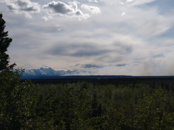 Photo shows a view of Oregon Lakes Fire activity on 5-30-19 from a rest area along the Richardson Highway. Large mountains are visible in the distance with smoke in the foreground.