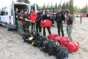 BLM Alaska Fire Service Chena Interagency Hotshots unload their gear shortly arriving at a staging area for the Oregon Lakes Fire Sunday night. The Midnight Sun and Chena Hotshots are joining the suppression efforts on the fire today. Photo by Beth Ipsen, BLM AFS