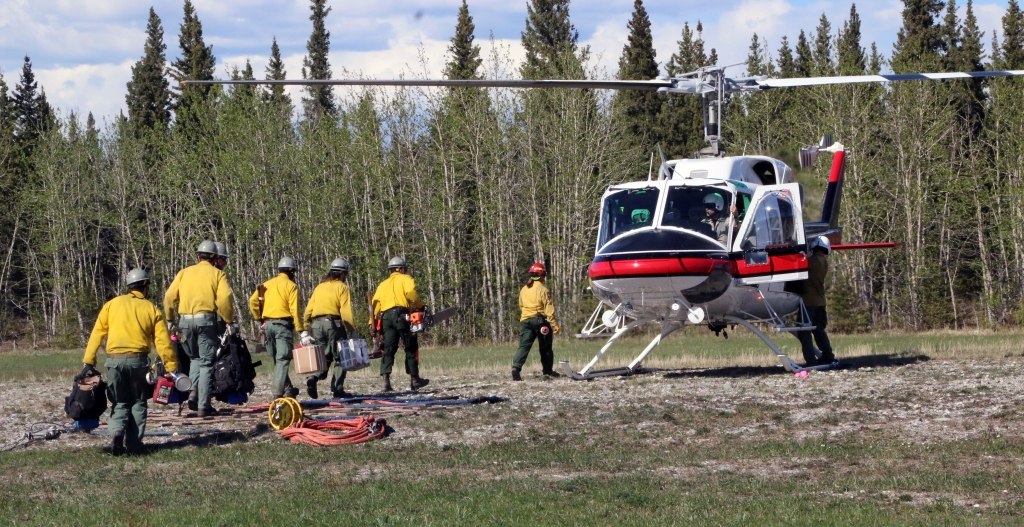 Photo of Pioneer Peak Interagency Hotshot Crew firefighters walking to a helicopter that will shuttle to the fireline on May 15, 2019.