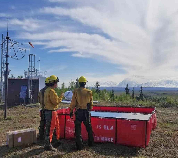 Photo of Type 2 Emergency Firefighter Fairbanks #1 Crew checking water levels in a portatank installed as part of structure protection at military observation sites while the crew was assigned to the fire May 17-22.