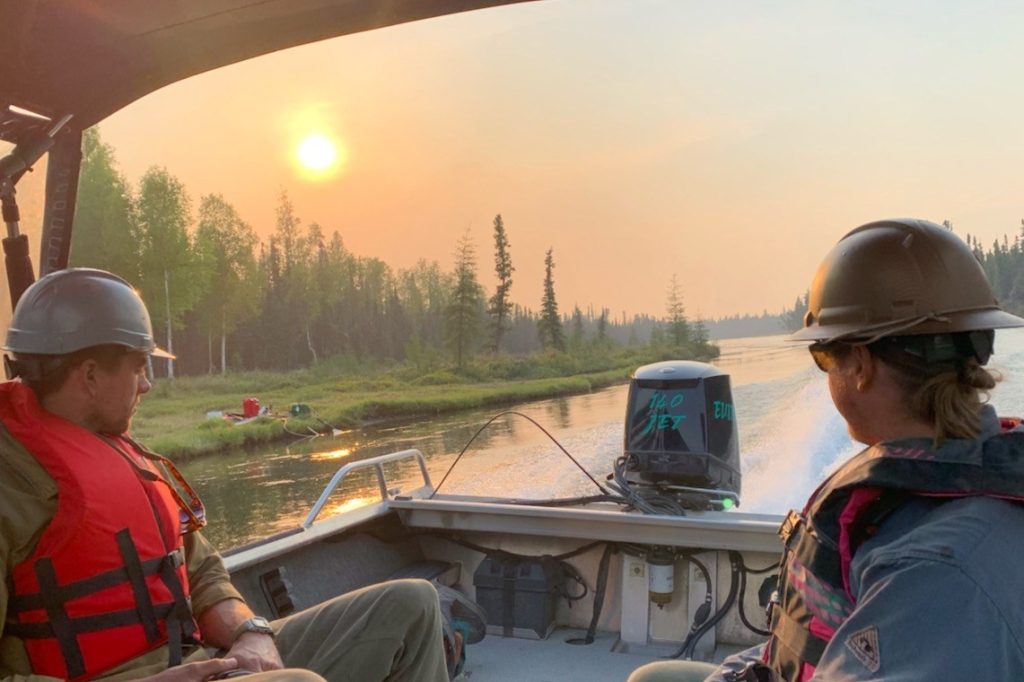 Photo shows two BLM Alaska Fire Service Smokejumpers riding in a boat looking out at the river, trees and smoky sky. Pumps and hose are in the background. Photo by Alaska Smokejumper Travis McCabe.
