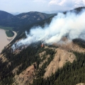 A fire burning on a very steep bank with the Yukon River below and hills in the background. In the foreground is a mix of trees and rocky areas.