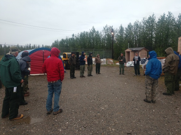 Photo of a group of firefighting personnel receiving their briefing on a rainy morning. Supplies and other equipment are in the background. The briefing is not only for those pictured, it is also transmitted by radio to those in the field or on the line. Photo by Maggie Demers.