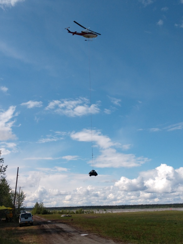 A helicopter hovers above a field with a UTV in a cargo net hanging below, just as it is setting it down. The river and puffy white clouds are in the background.