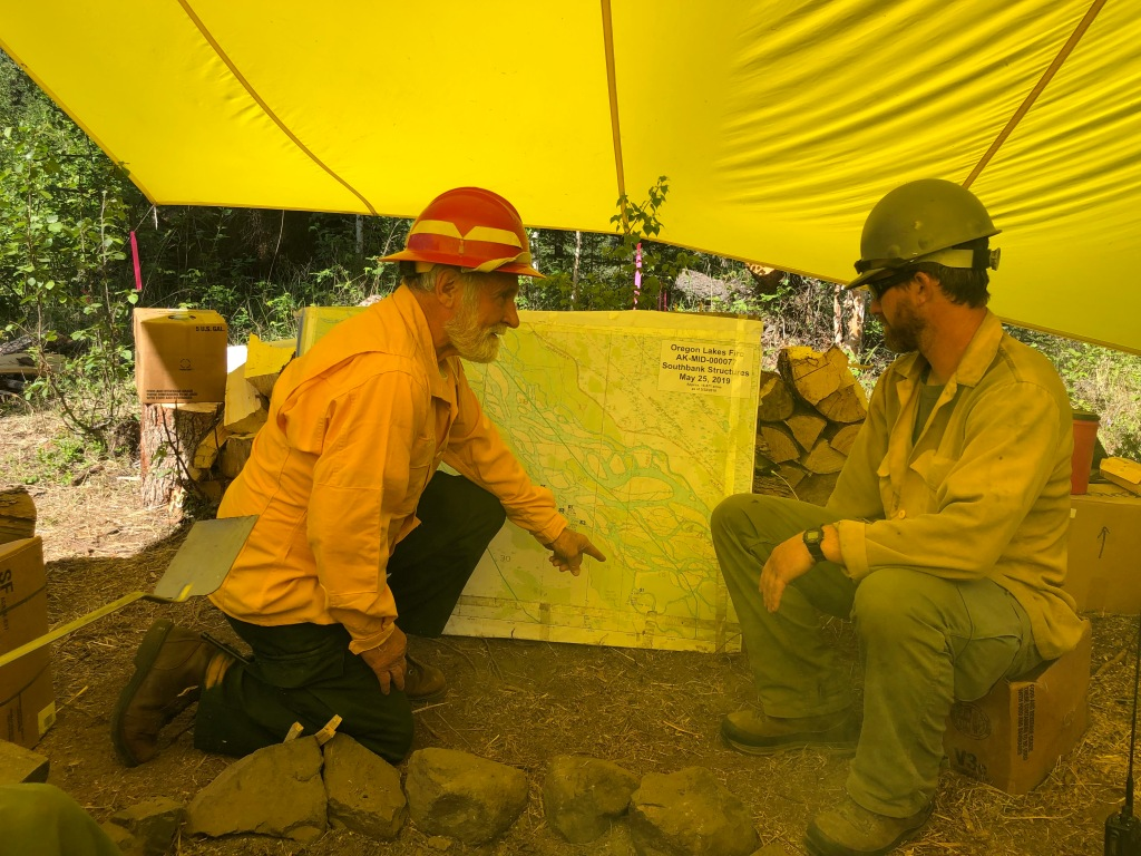 Safety Officer Larry Dorshorst and Division Supervisor Tim Hatfield compare notes at the South Bank camp. Photo credit: BLM Alaska Fire Service
