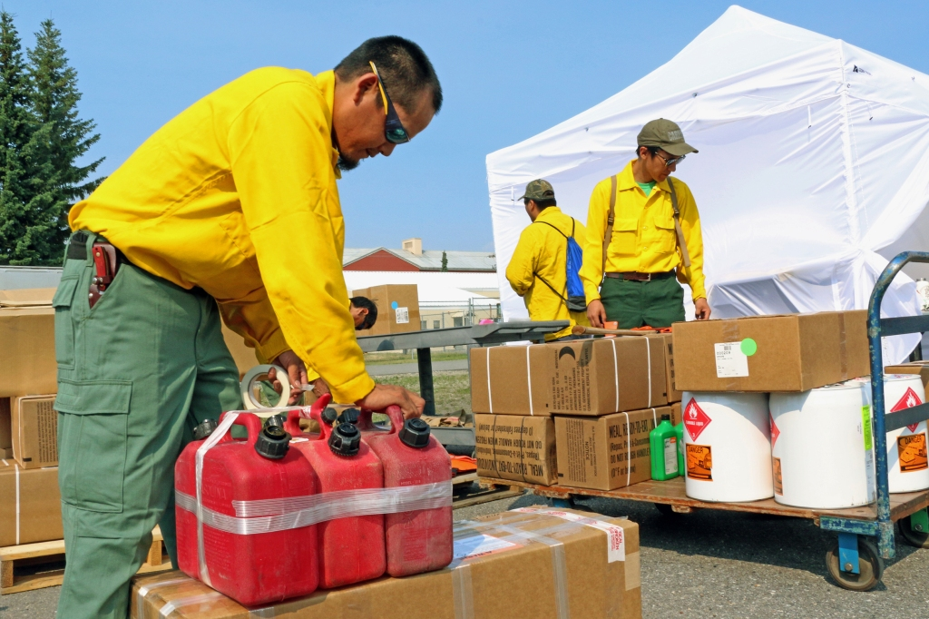 Rolland Linus of Allakaket taps up a set of dolmars gas can for chainsaws while he and a squad of BLM AFS emergency firefighters mobilize for a Black River Fire (#262) burning in the Upper Yukon Zone on June 28, 2019. Nicholas Cleveland of Hughes, in back, also helps organize the squad's gear.