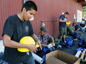 Erick John, a Yukon Flats Type 2 Crew firefighter from Venetie, puts together his hard hat while mobilizing with the rest of his crew at the Division of Forestry State Fire Warehouse in Fairbanks. Fellow crew members, behind him, Gabriel Simple and Donald Tritt are busy putting their packs together before they're bused to the Caribou Creek Fire burning north of Two Rivers on June 21, 2019. Photo by Beth Ipsen, BLM AFS