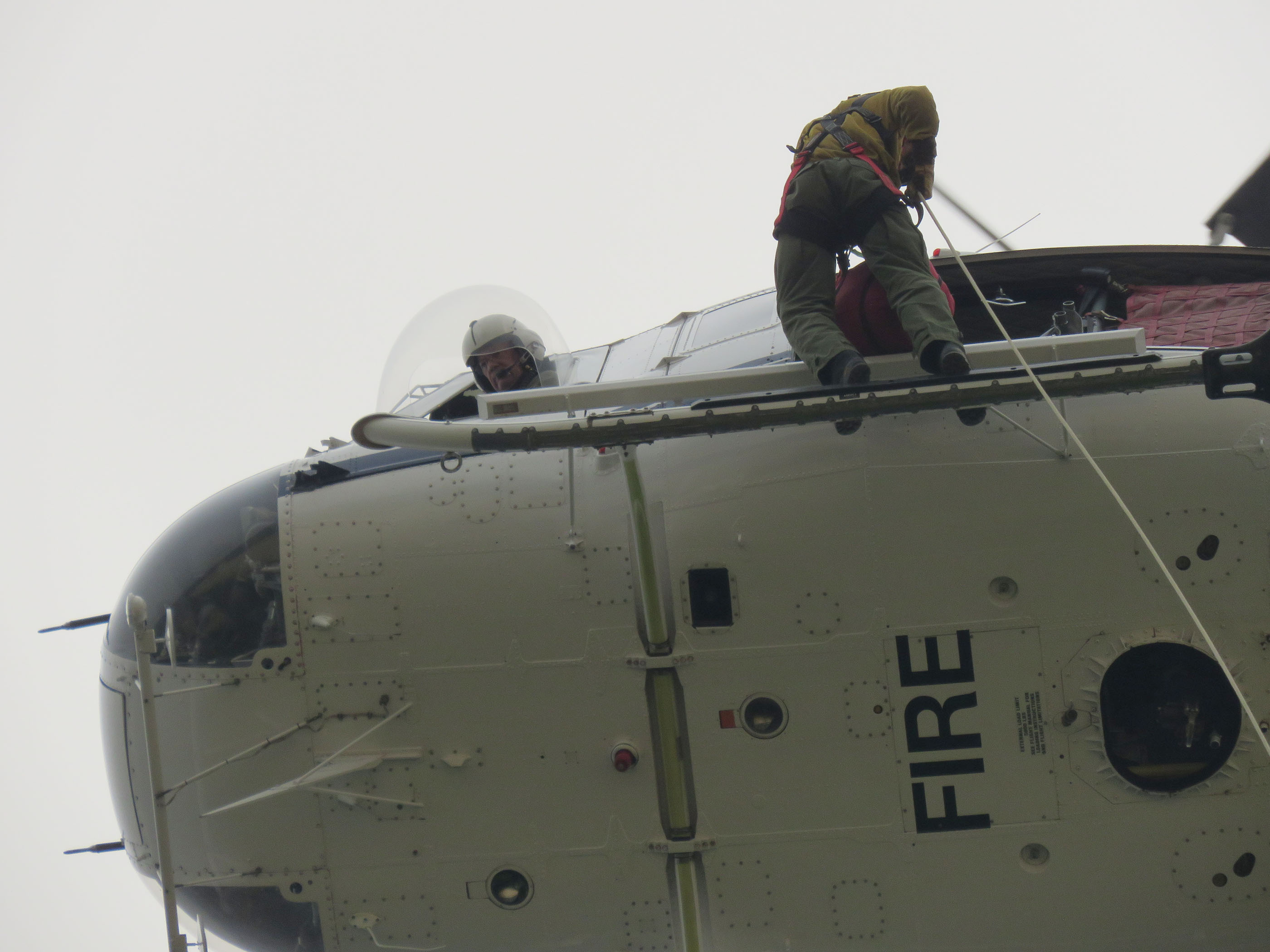 A firefighter standing on the skid of a helicopter prepares to descend on a rope as the pilot watches the ground from a window.