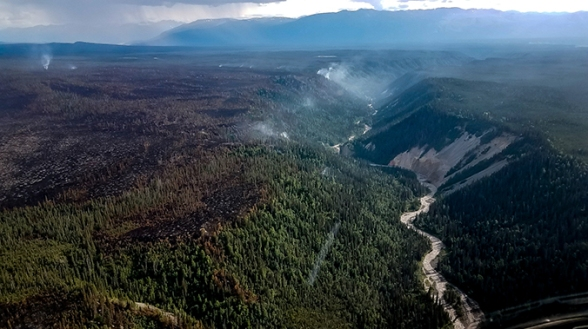 Aerial view of the Chetaslina Fire (#606) showing burned area, green vegetation, minimal smoke, and rain in the distance.