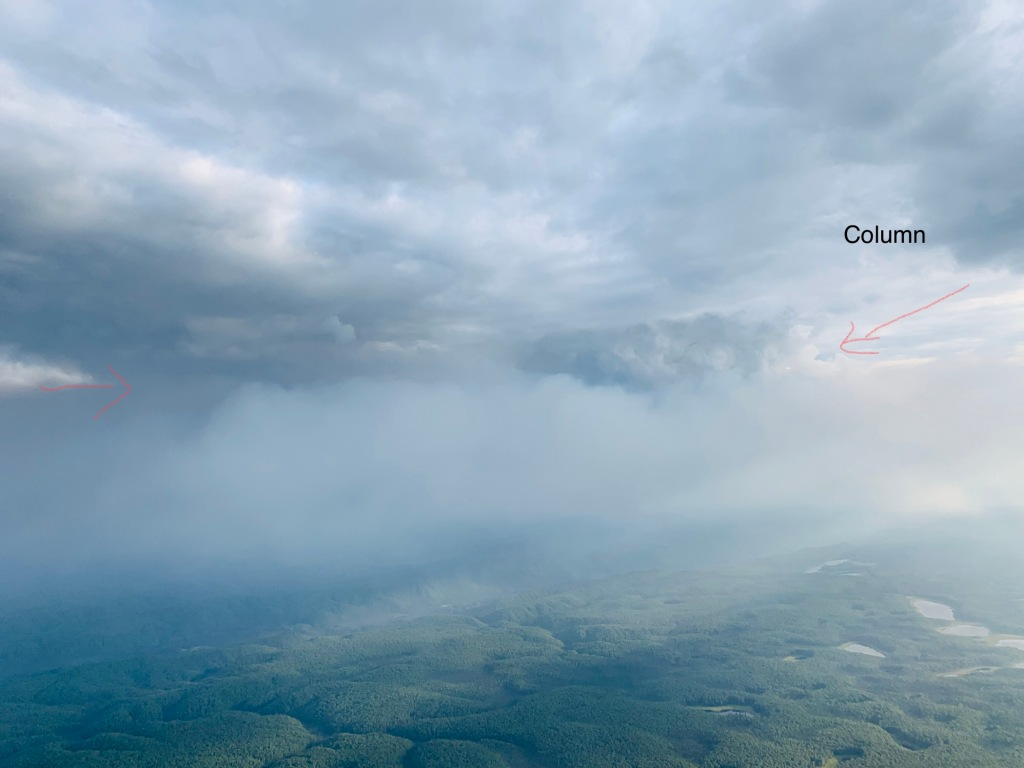 Photo of smoke rising through clouds above Little Mud River Fire Monday sent ash blowing 10 miles northeast to Manley.