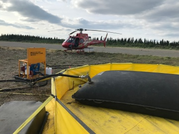 Photo of helicopter and fuel bladder at the Village of Beaver. The helicopter is used for operations on the Tony Slough and Hadweenzic fires. Photo by Bea Day, Portland National Incident Management Organization (NIMO)