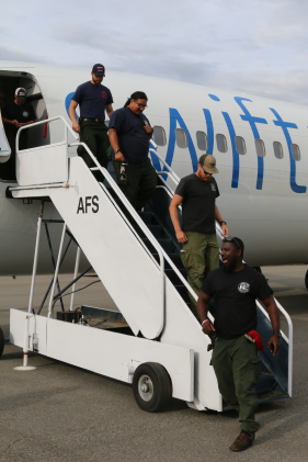 This picture depicts firefighters walking down the stairs from a passenger jet onto the airport tarmac.