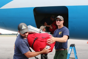 This picture depicts firefighters moving bags of their personal gear out of the cargo hold of an aircraft.