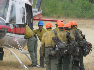 A line of firefighters prepares to board a helicopter in a grass field.