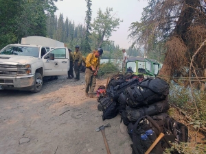 Members of the Alaska Division of Forestry's Gannett Glacier Type 2 Initial Attack Crew prepare to load their gear onto a jetboat to be transported across the Klutina River to the Klutina River Fire on Wednesday, July 10, 2019. Photo by Danny Schmitz