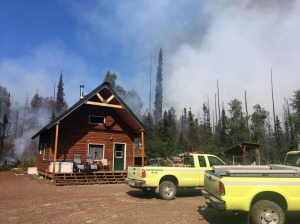 Two Alaska Division of Forestry engines sit in front of a home with smoke from the Malaspina Fire rising in the background on Sunday, July 7, 2019. Photo by Brentwood Reid/Alaska Division of Forestry