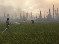 Photo of Alaska smokejumpers from left to right, Brandon Kobayashi, Russell Kennedy, Kristopher Dudley conducting a burn operation in the marsh below Jim Magdanz and Susan Georgette's cabin on the Mauneluk River Wednesday on July 17, 2019. Photo courtesy Jim Magdanz