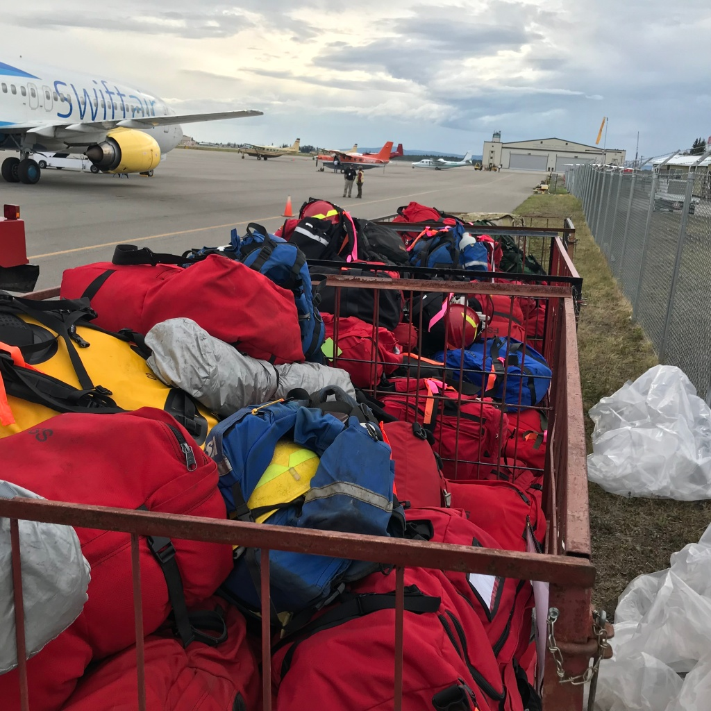 Red and blue bags of personal gear and firefighting equipment piled on the edge of tarmac near firefighting aircraft