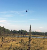 A helicopter dips water out of a pond to dump on the Montana Creek Fire with Denali in the background. Photo by Stephanie Bishop/Alaska Division of Forestry