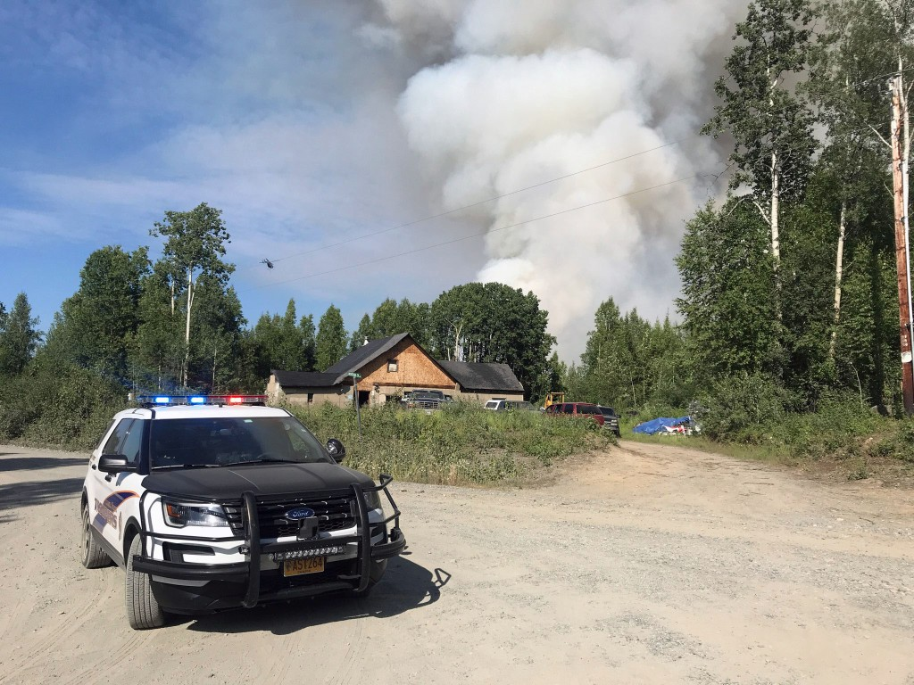 An Alaska State Trooper vehicle sits in front of a house with the smoke column from the Montana Creek Fire rising in the background. Photo by Sgt. Brent Johnson/Alaska State Troopers