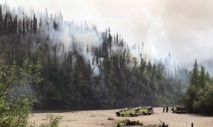 Firefighters from the Alaska Division of Forestry's Fairbanks Area office watch from a gravel bar as the Nugget Creek Fire backs down a hillside toward the Chena River near Mile 37.7 Chena Hot Springs Road on Sunday, June 30, 2019. Photo by Meg Cicciarella/Alaska Division of Forestry