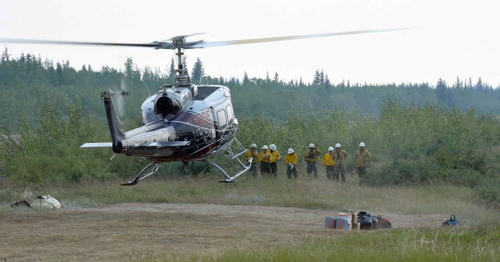 A bell 205 helicopter lands to pick up waiting members of the Chief Mountain Hotshot Crew at the Chalkyitsik helibase Sunday, July 14, 2019. The crew was being transported to the Chahalie Lake area near the Frozen Calf Fire (#367). The crew from Montana completed an assignment on the Shovel Creek Fire (#319), returned home for two days off and are now back in Alaska. Sam Harrel/Alaska Interagency Incident Management Team