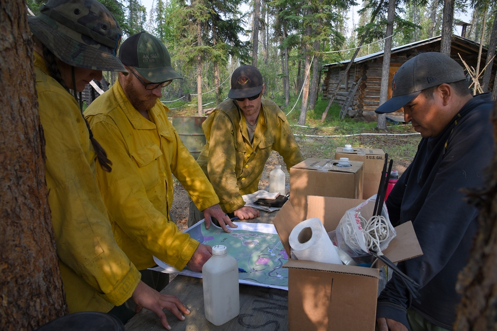 Photo of Division Supervisor Billy McCall, second from left, gives an operational update to Missoula Smokejumpers Emma Hawn, left, and Brian Ries, middle, at a cabin site along the Draanjik River on Monday afternoon, July 15, 2019. Boat operator Davis Carroll, right, listens in. Sam Harrel/Alaska Interagency Incident Management Team