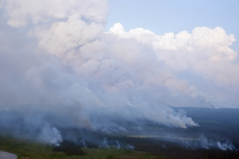 Columns of smoke rise Thursday evening, July 18, 2019, from where a helicopter has dropped plastic spheres that ignite to catch a broad area black spruce on fire. The tactical firing operation is removing the fuels ahead of the Frozen Calf Fire (#367) to the northeast of Chalkyitsik. Sam Harrel/Alaska Interagency Incident Management Team